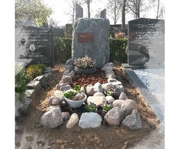 Grafsteen van ruwe stenen met bronzen plak voor de tekst