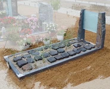 Grafsteen met glasplaat en keien
