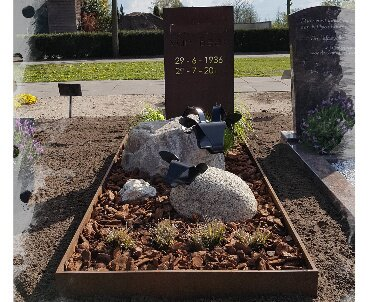 grafsteen met cortenstraal en schapen