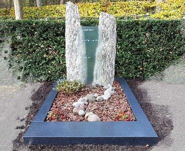 grafsteen met zuilen en glas