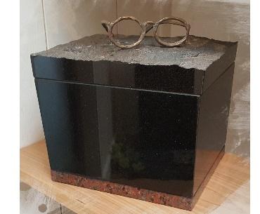 Urn van graniet met bronzen bril
