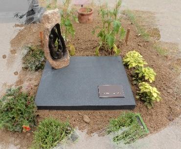 Kunstobject op algemeen graf met bronzen plak